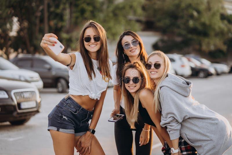 Fyra unga kvinnor som tar en selfie och att ha roligt arkivbilder