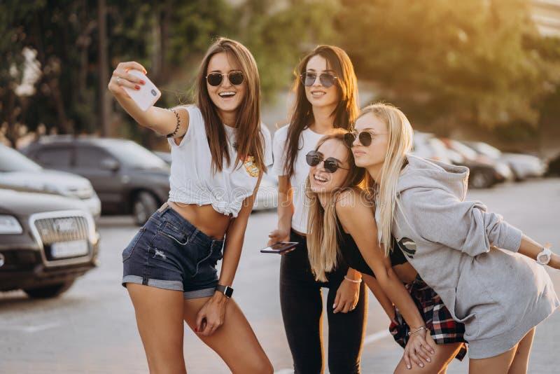 Fyra unga kvinnor som tar en selfie och att ha roligt royaltyfri bild