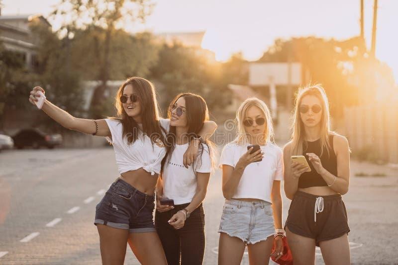 Fyra unga kvinnor som tar en selfie och att ha roligt royaltyfri foto