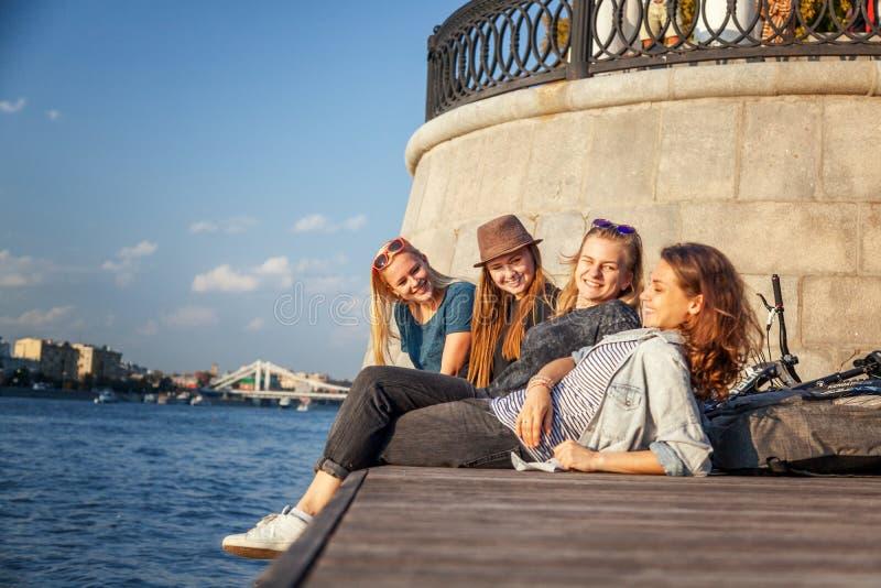 Fyra unga lyckliga flickvänstudenttonåringar vilar tillsammans på royaltyfri fotografi