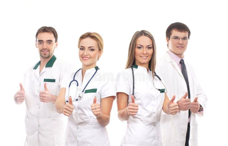 Fyra unga medicinska arbetare som rymmer upp tum royaltyfri fotografi