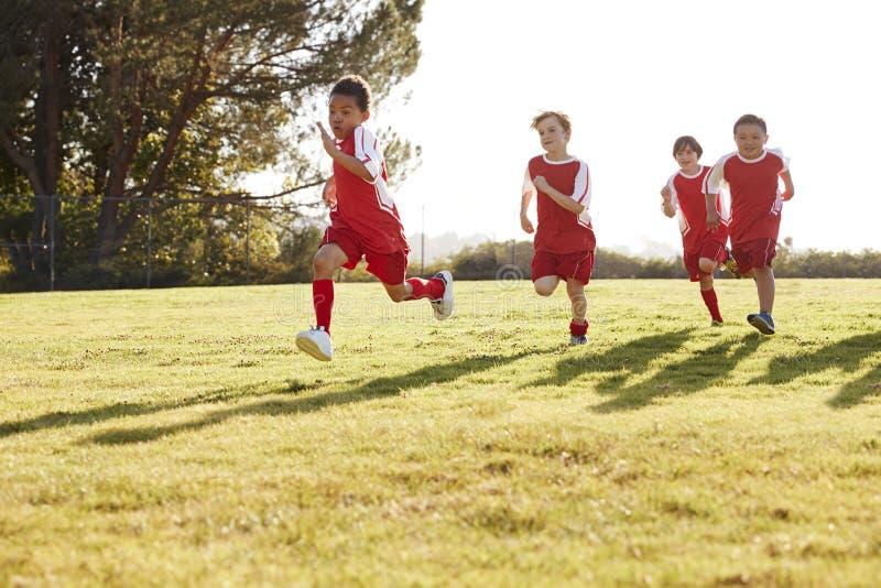 Fyra unga pojkar i fotboll river av spring i en spelplan arkivfoto