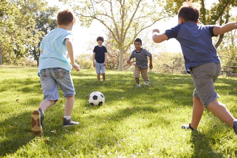 Fyra unga skolpojkar som spelar fotboll tillsammans i parkera royaltyfri bild