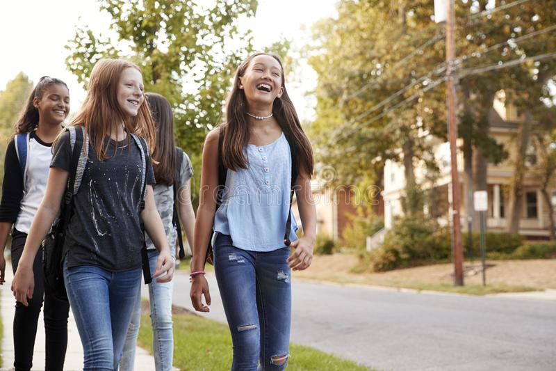 Fyra unga tonåriga flickor som går till skolan, slut för främre sikt upp fotografering för bildbyråer