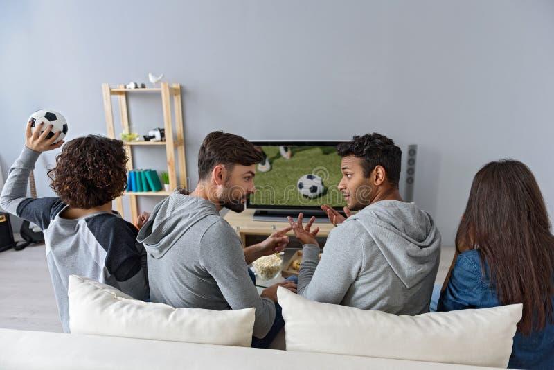 Fyra unga vänner som underhåller med television royaltyfria foton
