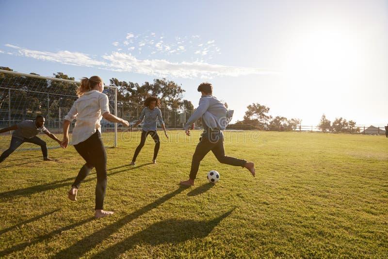 Fyra unga vuxna människor som spelar fotboll i en parkera på solnedgången arkivbild