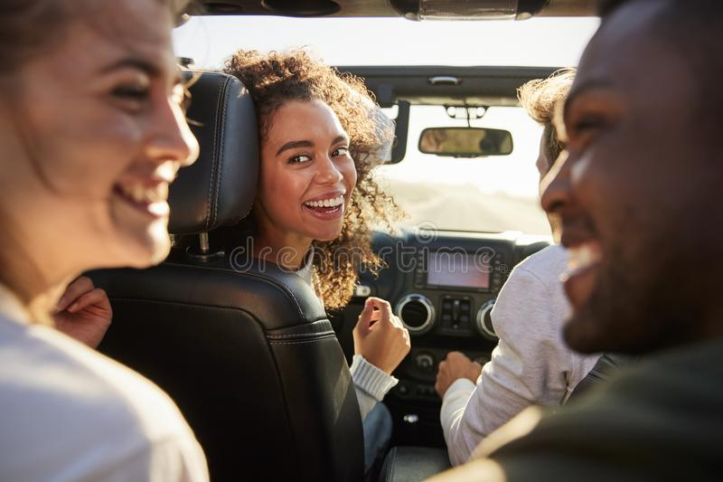 Fyra unga vuxna vänner i en bil på en vägtur tillsammans arkivbild