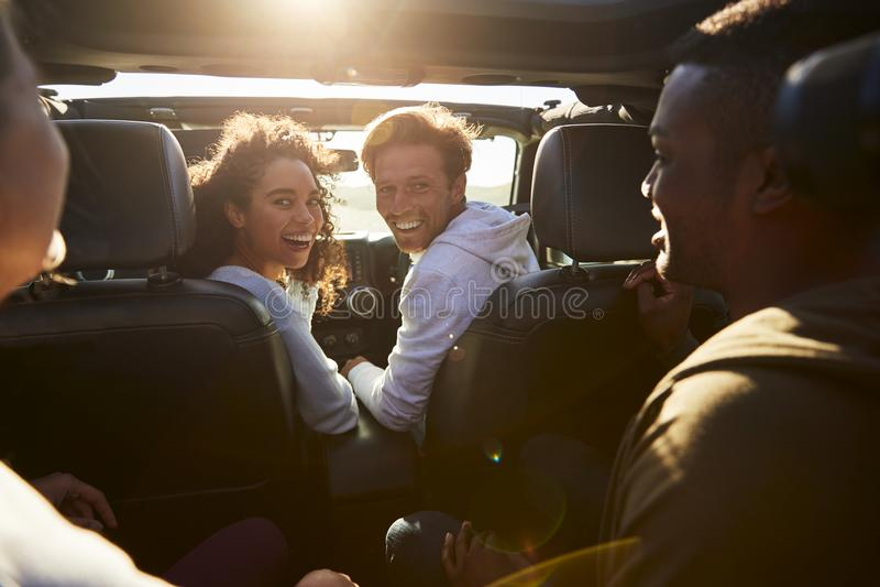 Fyra unga vuxna vänner som tillsammans reser i en bil arkivfoton