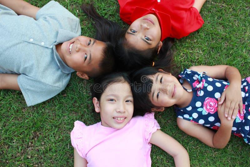 Fyra ungar som har gyckel i parkera royaltyfri fotografi
