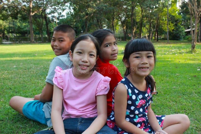 Fyra ungar som har gyckel i parkera royaltyfria bilder
