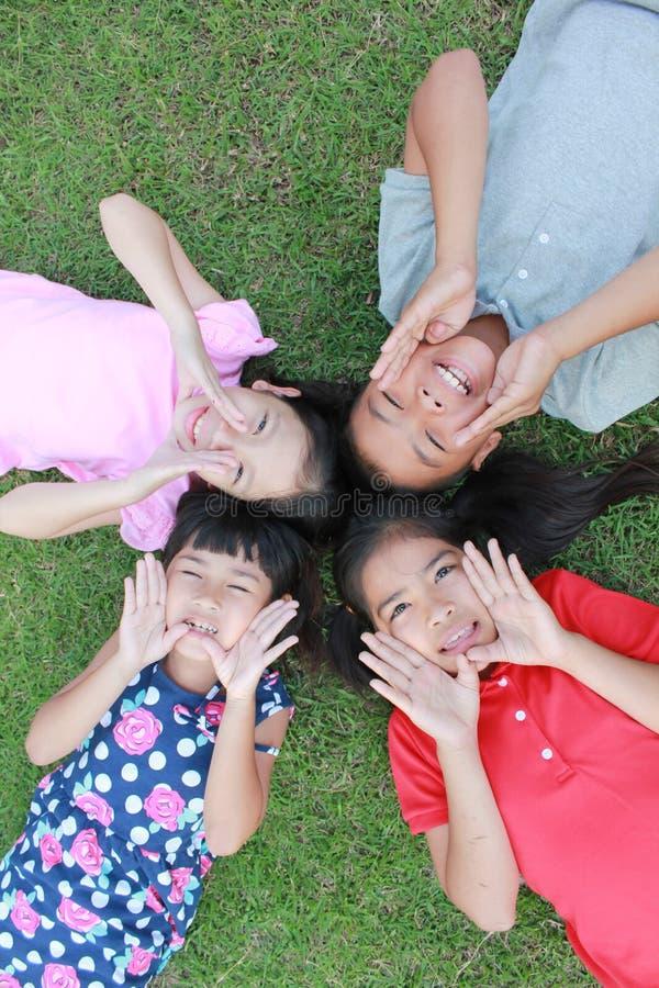 Fyra ungar som har gyckel i parkera arkivfoton