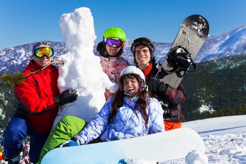 Fyra ungdomarmed snowboarden och snögubbe royaltyfri foto