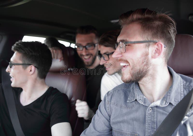 Fyra vänner i en bil som lämnar för semester royaltyfria foton