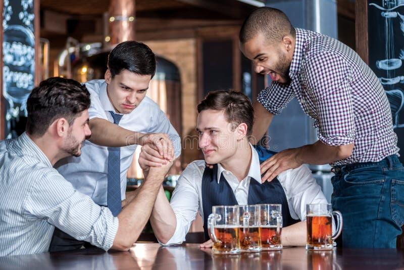 Fyra vänner kämpar på deras handdrinköl och spenderar tid t royaltyfri fotografi