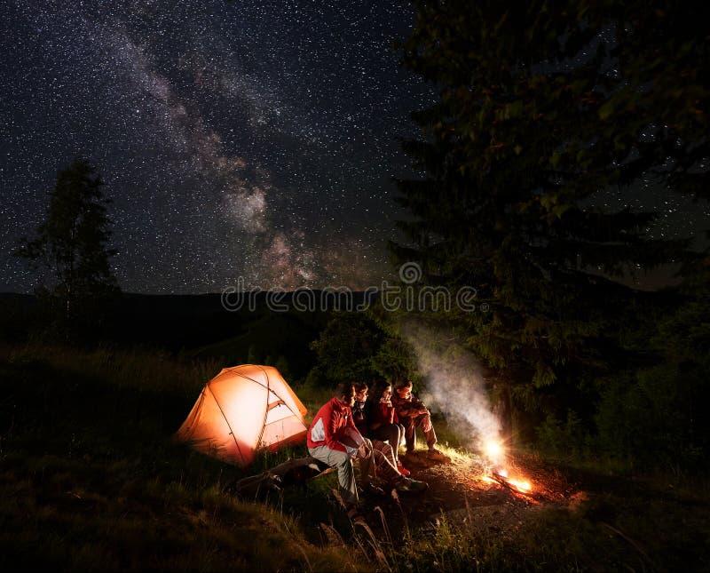 Fyra vänner sitter på journal nära tältet som tycker om flamman av brand nära de härliga granträden under stjärnklar himmel arkivfoton