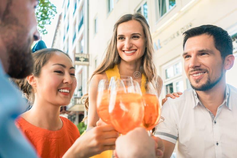 Fyra vänner som firar samman med en uppfriskande sommardrink arkivbild