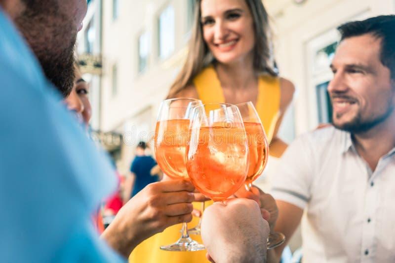 Fyra vänner som firar samman med en uppfriskande sommardrink royaltyfria bilder