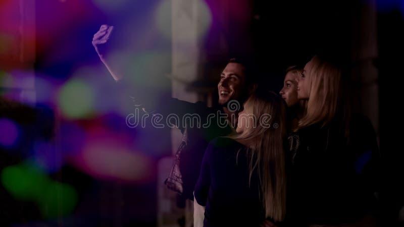 Fyra vänner som gör selfie på smartphonen på nattklubben, kamratskap och lycka royaltyfria foton