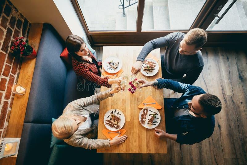 Fyra vänner som rostar i en restaurang Top beskådar royaltyfria foton