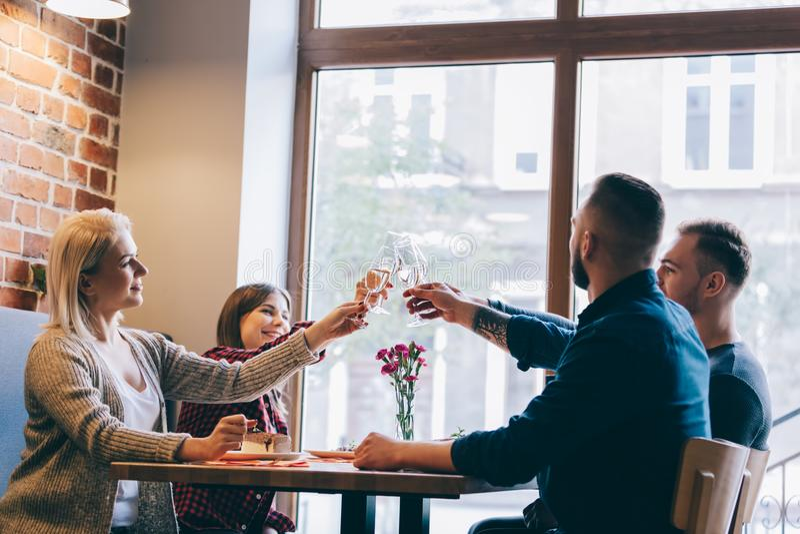 Fyra vänner som sitter samman med exponeringsglas av champagne royaltyfri foto