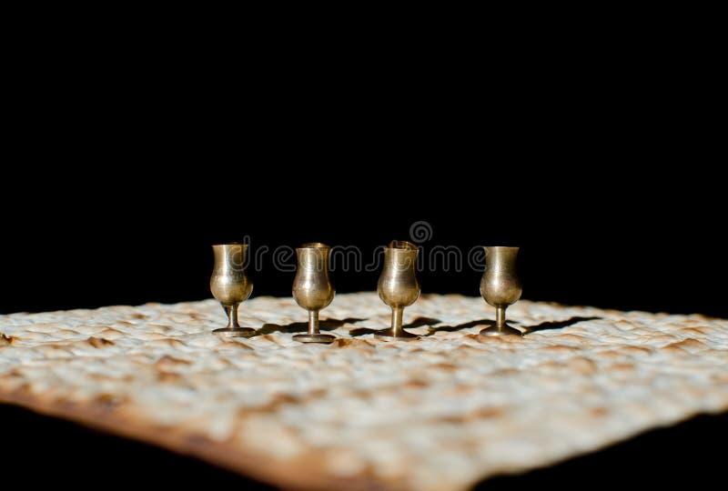 Fyra vinminiatyrkoppar och matzah för den judiska påskhögtiden arkivfoton