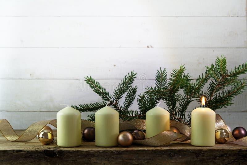 Fyra vita stearinljus, ett av dem bränning på den första adventchrien arkivfoton