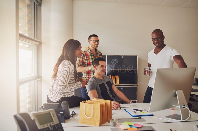 Fyra vuxna människor som sitter runt om skrivbordet på arbete arkivbild