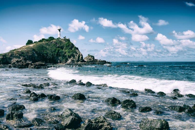 Fyren på berget med vågor som sopar in mot den steniga kusten arkivfoton