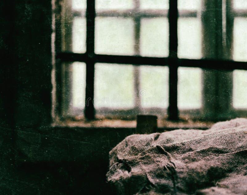 Fyrkant skrapat fängelsefönster med britsen royaltyfri bild