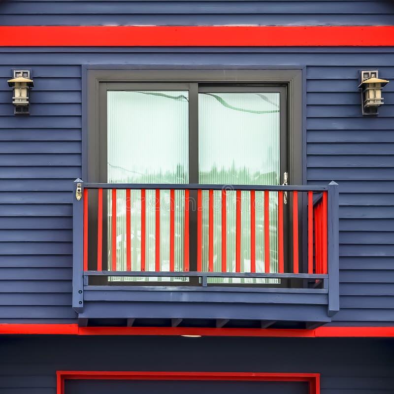Fyrkanten stänger sig upp av hem- yttersida med röda ramar för den vibrerande blåa väggen och den lilla balkongen royaltyfri fotografi