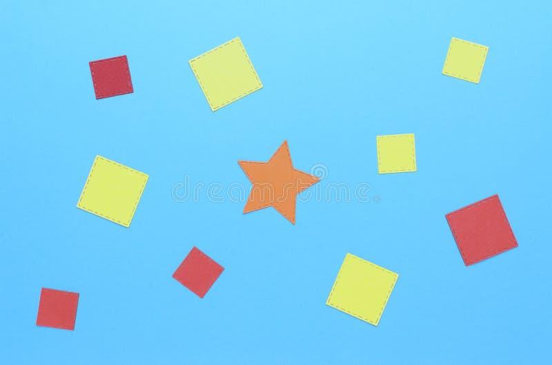 Fyrkanter av papper och en orange stjärna i mitten royaltyfria bilder