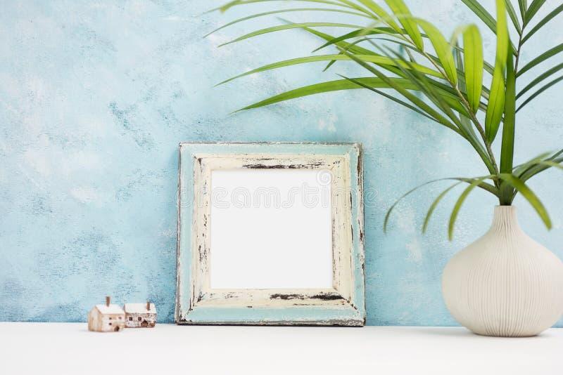Fyrkantig blå fotoramåtlöje upp med gröna tropiska växter i små trähus för vaseand på hylla Skandinavisk stil arkivbild