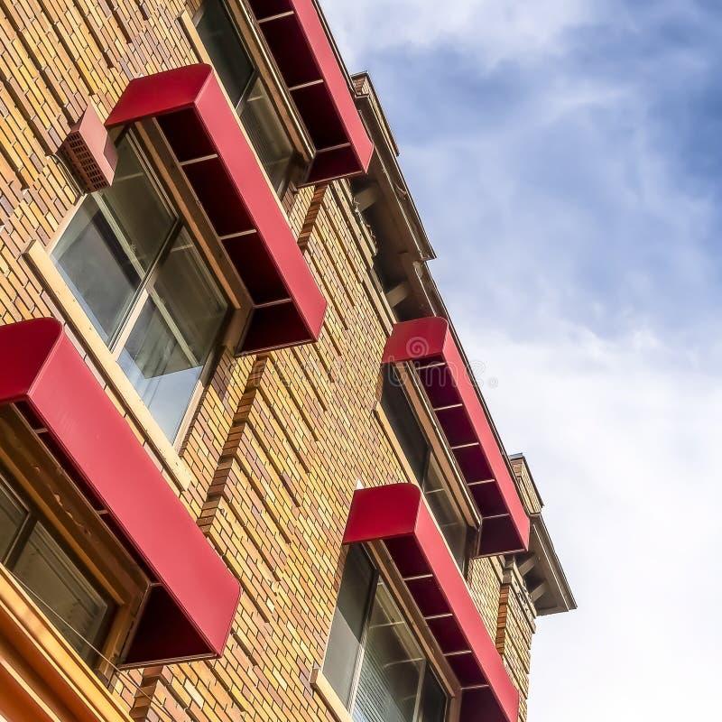 Fyrkantig byggnad med den gula väggen för stentegelstenyttersida och röda markiser på fönstren royaltyfri bild