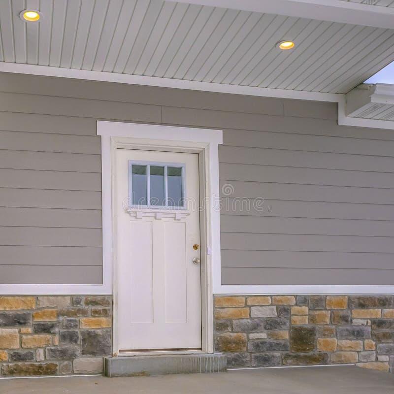 Fyrkantig fasad av ett hem med trappa som leder till farstubron och den exponeringsglas försåg med rutor ytterdörren arkivbild