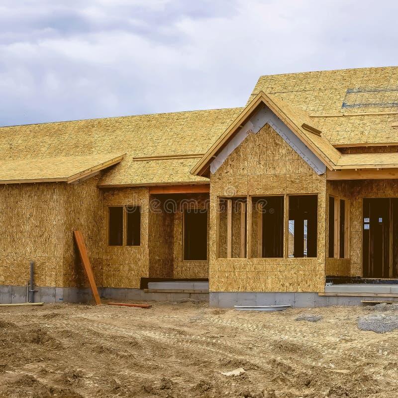 Fyrkantig fasad av hemmet under konstruktion mot det snöig berget och molnig himmel royaltyfria foton