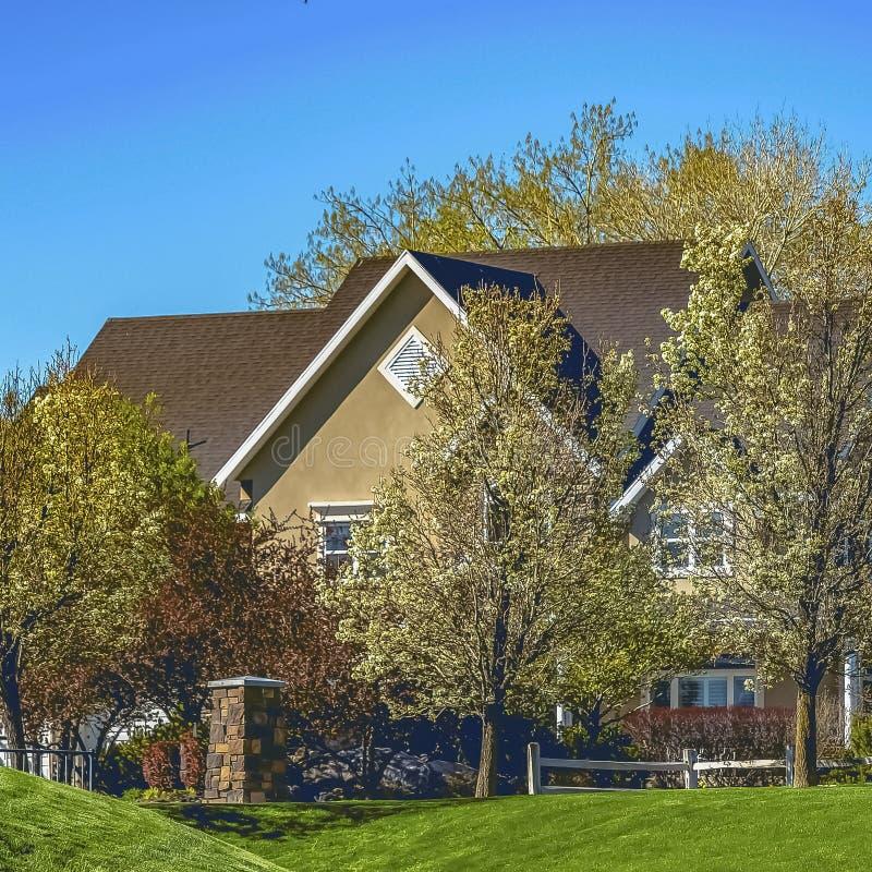 Fyrkantig fasad av huset på den vidsträckta gräs- terrängen under klar blå himmel på en solig dag royaltyfri foto