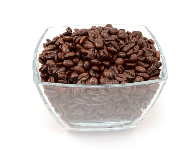 Fyrkantig glass bunke mycket av grillade kaffebönor fotografering för bildbyråer