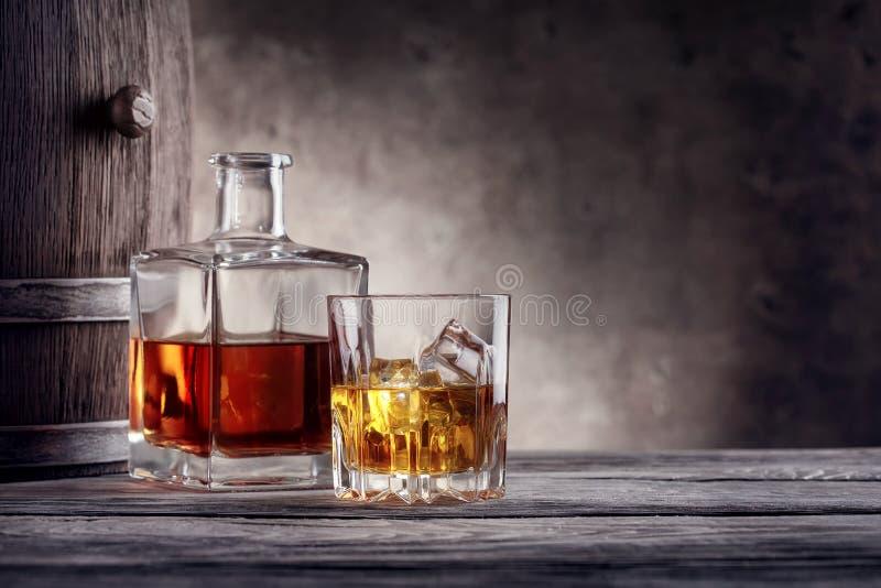 Fyrkantig karaff och ett exponeringsglas av whisky med is arkivfoto
