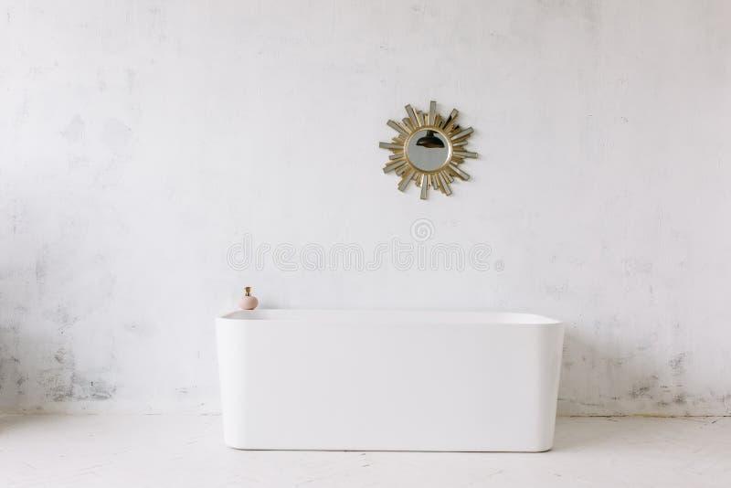 Fyrkantig ram av det moderna badrummet med det fristående vita badkaret på lantlig väggbakgrund för vind med solformspegeln arkivbild
