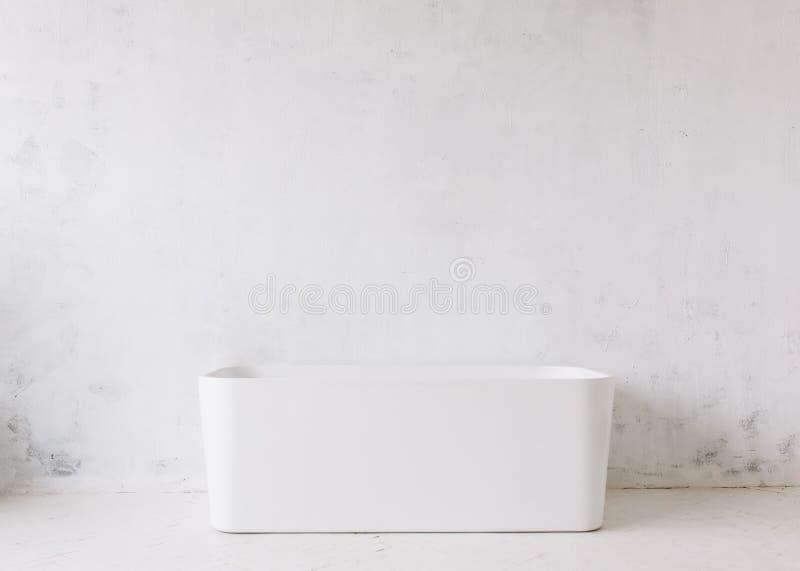 Fyrkantig ram av det moderna badrummet med det fristående vita badkaret på lantlig väggbakgrund för vind med solformspegeln arkivfoton