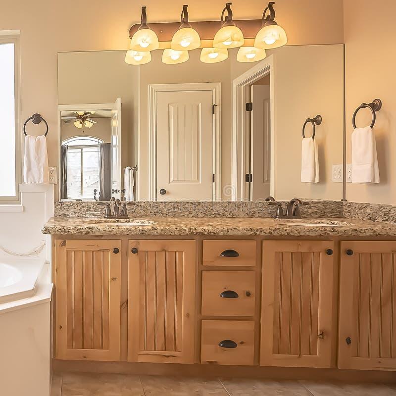 Fyrkantig ram som byggs i badkar på hörnet av ett hem- badrum med tegelplattagolvet och den beigea väggen arkivbilder