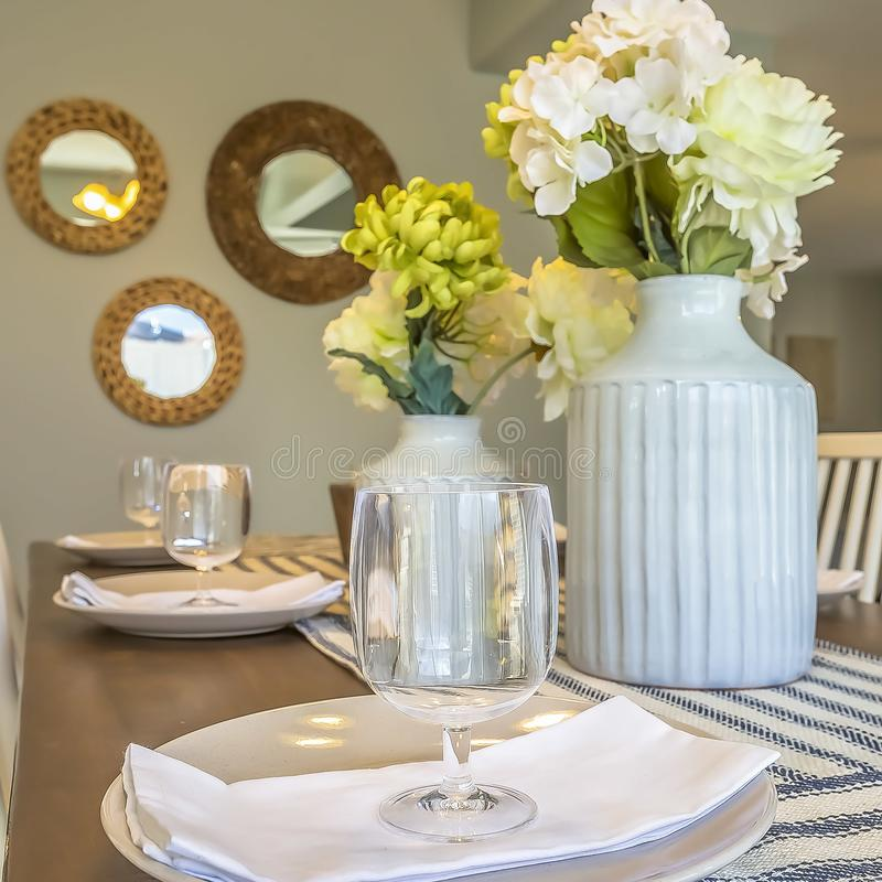Fyrkantig rammatställeinställning inom matsalen av ett hem med speglar och väggbakgrund fotografering för bildbyråer