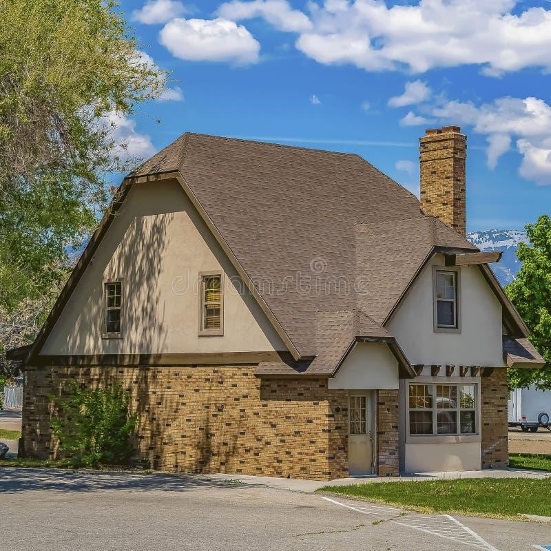 Fyrkantig ramyttersida av ett hem med fönster och lampglaset för mörkt tak för tegelstenvägg skinande arkivfoto