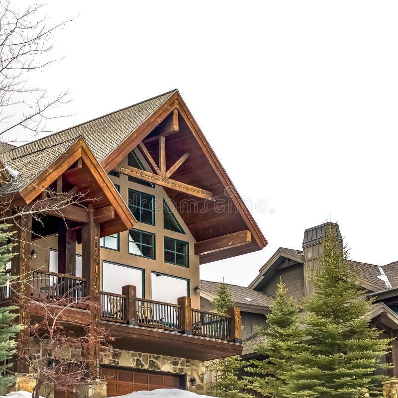 Fyrkantig yttersida av ett härligt trähus under ny snö på en molnig vinterdag arkivfoton
