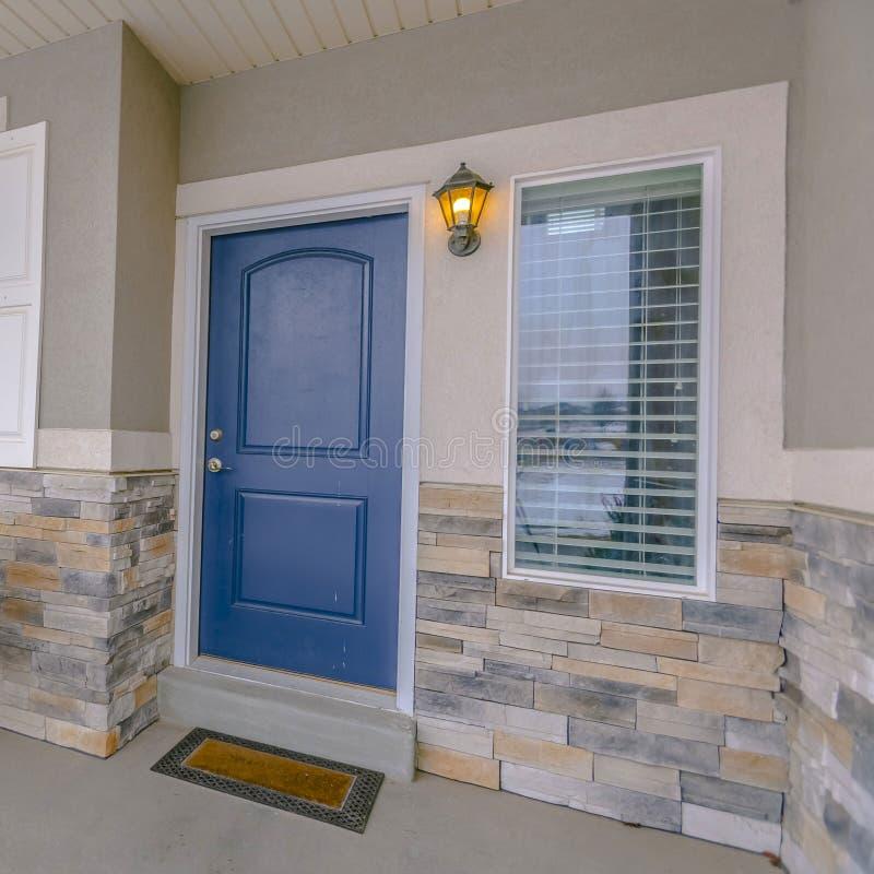 Fyrkantig yttersida av ett hem med den blåa träytterdörren och reflekterande exponeringsglasfönster royaltyfri foto