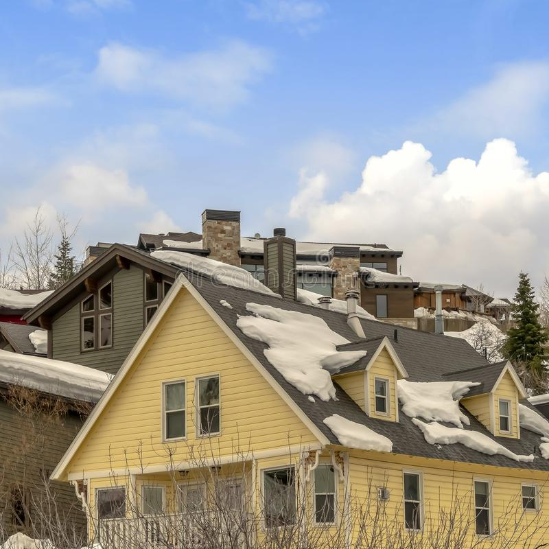 Fyrkantiga hus på dold jordning för snö mot blå himmel med pösiga moln i vinter fotografering för bildbyråer