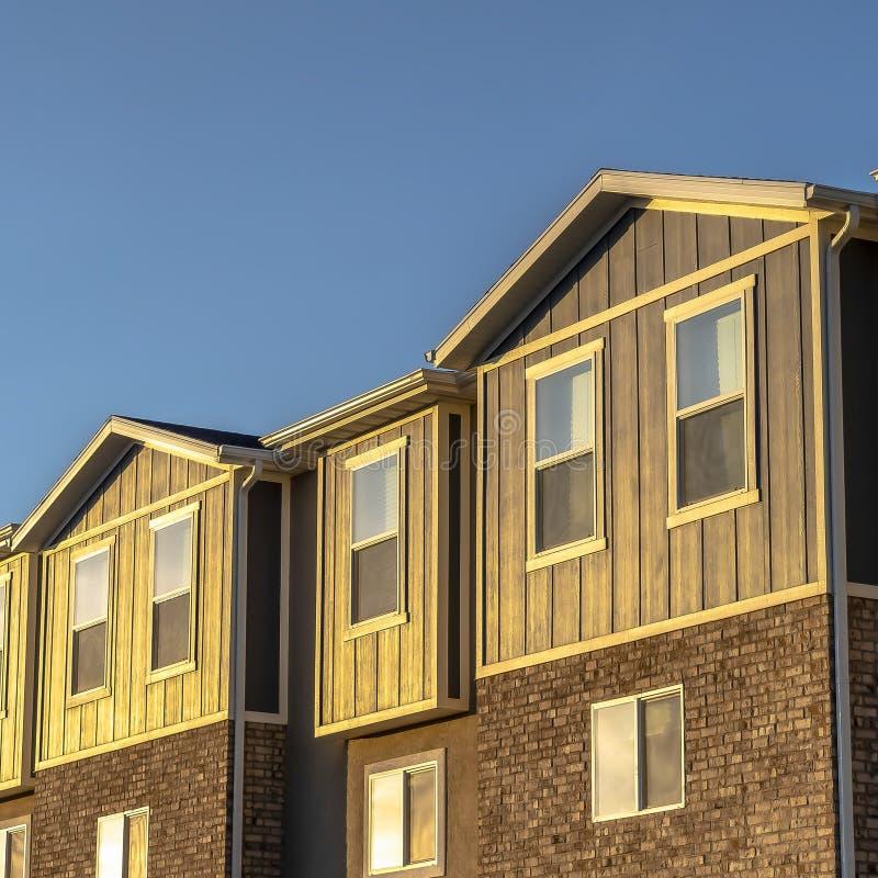 Fyrkantiga ramradhus med kombination av den trätegelsten och betongväggen på en solig dag arkivfoto