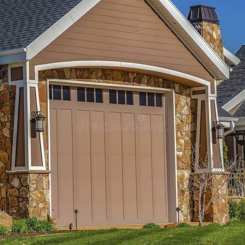 Fyrkantigt hem med främre gräsmatta för garagedörr och metallporten som beskådas mot klar blå himmel fotografering för bildbyråer