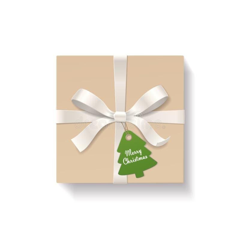 Fyrkantigt kraft gåvaask, fnuren för silverfärgpilbåge och band med etiketten för gran-träd formhängning Text för glad jul på grä stock illustrationer