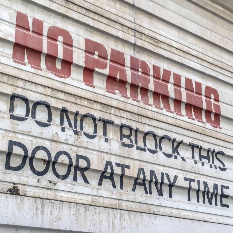 Fyrkantigt ramslut upp av inget parkera tecken som målas på den korrugerade metalldörren av en byggnad fotografering för bildbyråer
